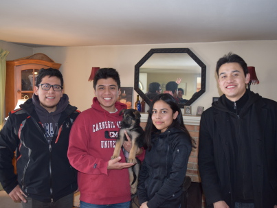 Four people with their new German Shepherd puppy